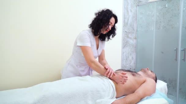 Krásné ženské terapeut dělá relaxační masáž na mužské břicho ve spa salonu
