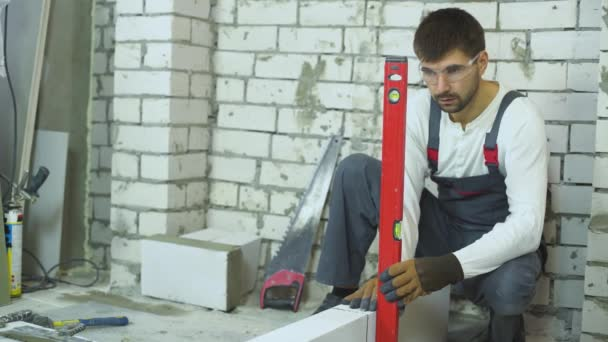 builder fixing brick laying with rubber hammer according to bubble level