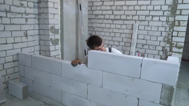 young caucasian builder checking evenness of newly built wall with bubble level