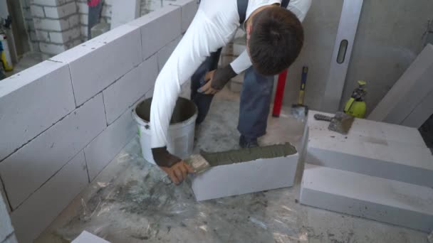high angle shot of builder putting mortar on side of aerated concrete block