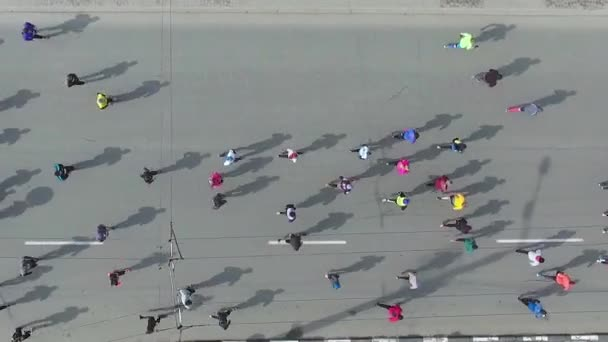 aerial top down shot of crowd of runners running during marathon on city road