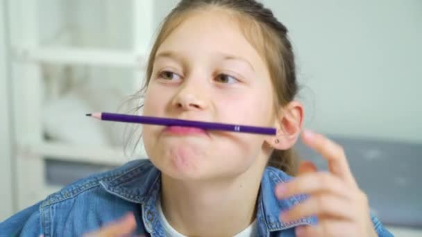 funny girl looking at camera and making faces with colored pencils