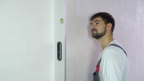 bearded builder checks evenness of new wall with bubble level with free space