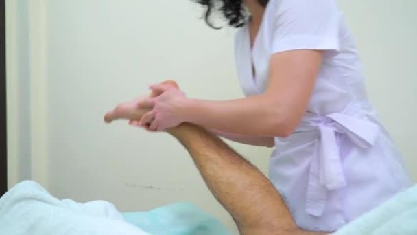 female masseur in uniform doing foot massage for male customer in spa salon