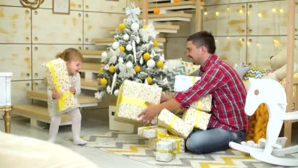 Kleinkind Mädchen mit Vater setzen Geschenk-Boxen unter geschmückten Weihnachtsbaum zu Hause