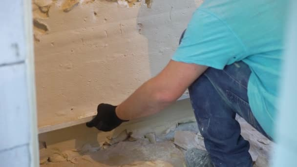 construction worker leveling plaster on wall at renovation site