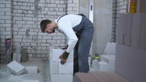 young builder laying aerated concrete block and checking it with bubble level