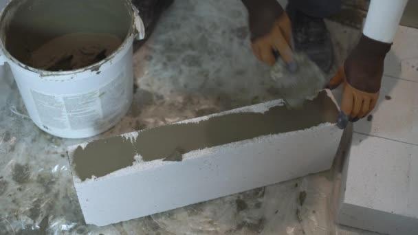 Hochwinkelaufnahme der Builder-Hände, die Mörtel auf Blockseiten mit Spachtel setzen