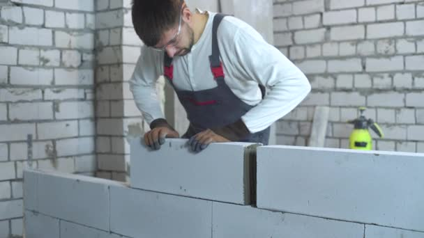 cheerful young builder in work wear laying blocks at construction site