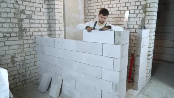 Kaukasischer Bauunternehmer in Arbeitskleidung verlegt Block und überprüft ihn mit Blasenpegel