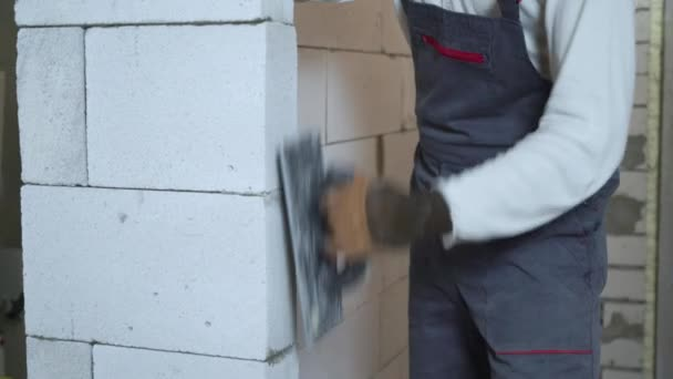 tilt shot of young builder in work wear grinding block wall with abrasive tool