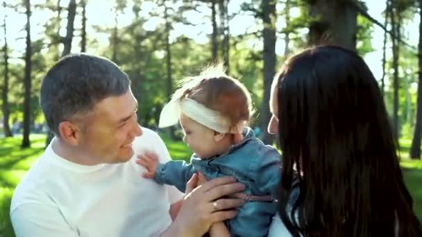 genitori felici tenere e baciare la loro piccola figlia allaperto con bagliore lente