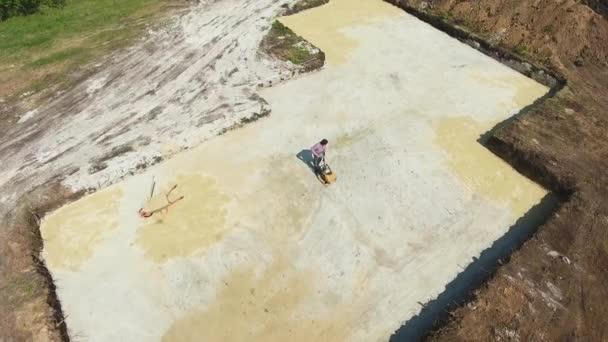 anténa pracovníka na písečném povrchu s vibrační deskou v jámě