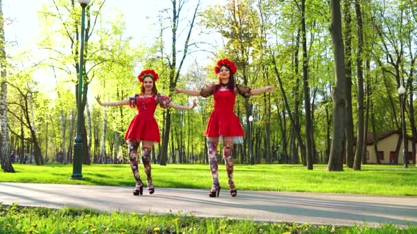 two women in folk styled costumes and circlets of flowers dance in sunny park