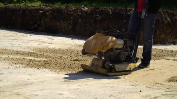 partial view of worker using vibratory plate compactor at construction site