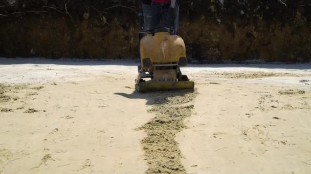 Stampfen von Sand mit Vibrationsplattenverdichter auf Baustelle des neuen Hauses
