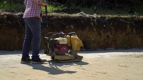 male worker ramming sand with plate compactor in foundation pit of new house