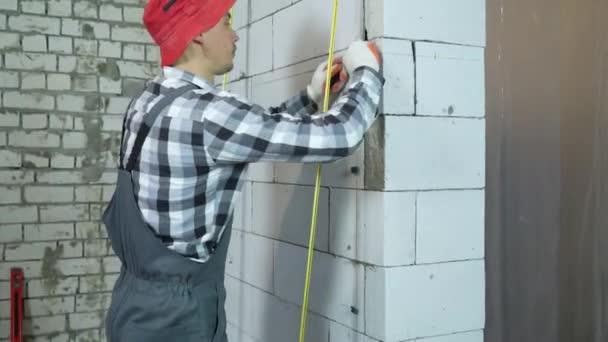 Kippschuss des Bauunternehmers, der Klemmen an Porenbeton-Blockwand installiert