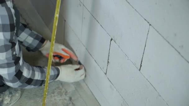tilt up shot of construction worker installing clamps on block wall