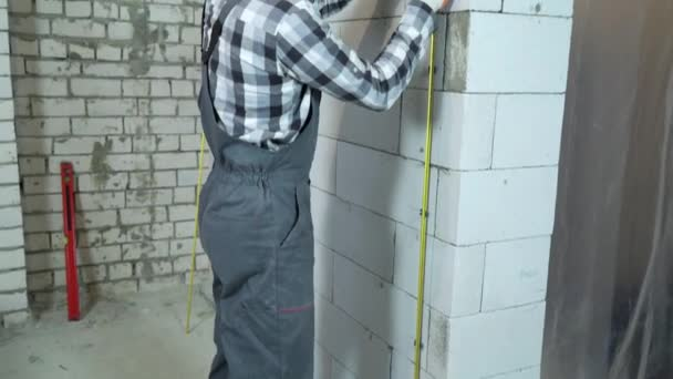 tilt shot of builder installing metal rails onto clamps on block wall
