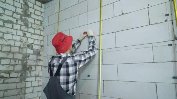 Bauarbeiter in Arbeitskleidung und roter Mütze schiebt Bauklammern in Blockwand