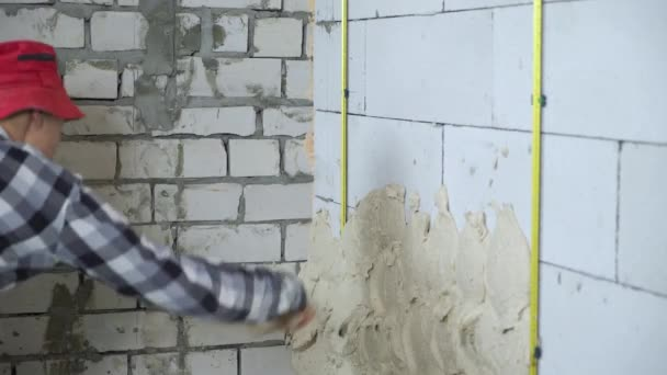cropped shot of builder plastering aerated concrete block wall
