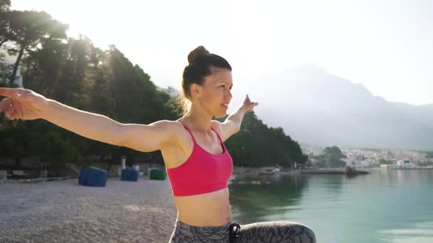 adult woman with hair bun practicing yoga at seaside in the morning