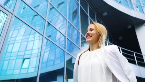 low angle of stylish blonde woman passing by modern building in slow motion