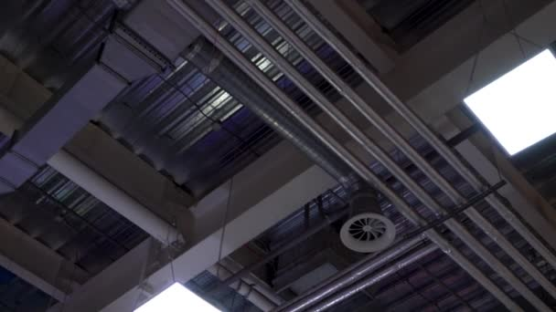 low angle of metal pipes of hvac system and lamps mounted to ceiling of big mall