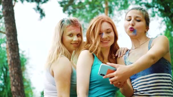low angle of three young women in Holi paints take selfie photo on mobile