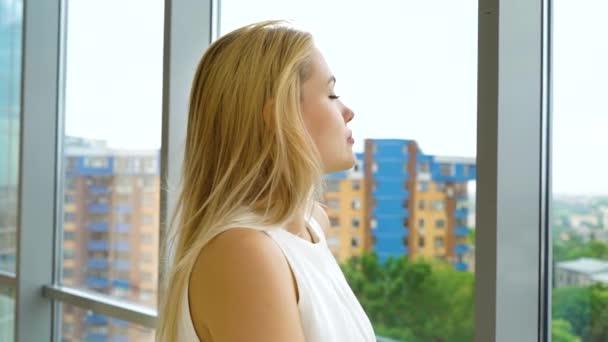 oddálit veselou blonďatou ženu, jak se dívá z okna na krajinu