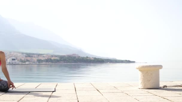 panoramic shot of yoga woman meditating in lotus pose on stone dock at seaside