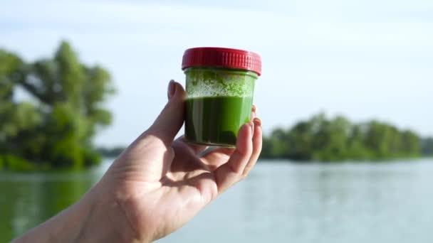 felvértezőre női kézben lévő konténer zöld algákkal és egy kicsit forgatható