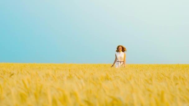 fröhliche rothaarige Frau im weißen Kleid springt in Zeitlupe in ein Weizenfeld