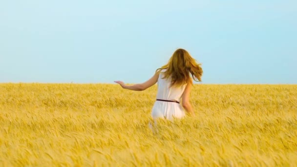 young happy red haired woman jumping and running in wheat field in slow motion