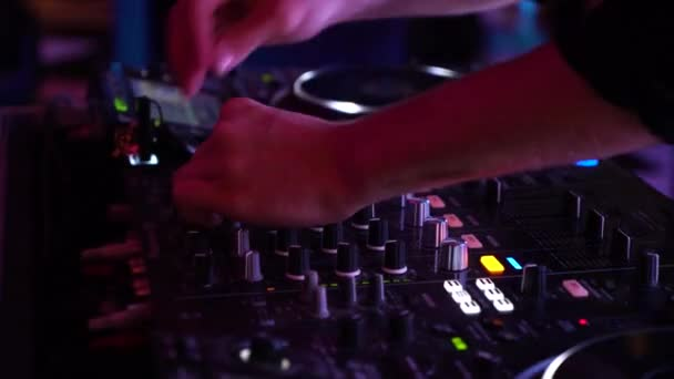 cropped shot of dj hands mixing music on mixer in flashing lights in night club