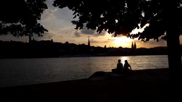 silhouette of young romantic couple having date on river pier at sunset