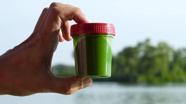 klokanou držením ruky a protřepáním nádoby se zelenými řasy uvnitř