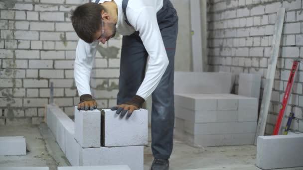 Bauarbeiter verlegt Porenbeton-Block und überprüft ihn mit Blasenfüllstand