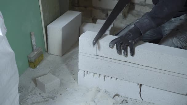 view of male builder hands sawing block with hand saw according to marking