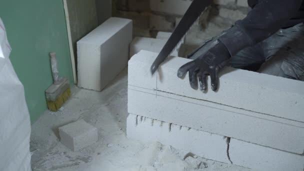 pohled na ruce mužského tvůrce řezání bloku s rukou pily podle značení
