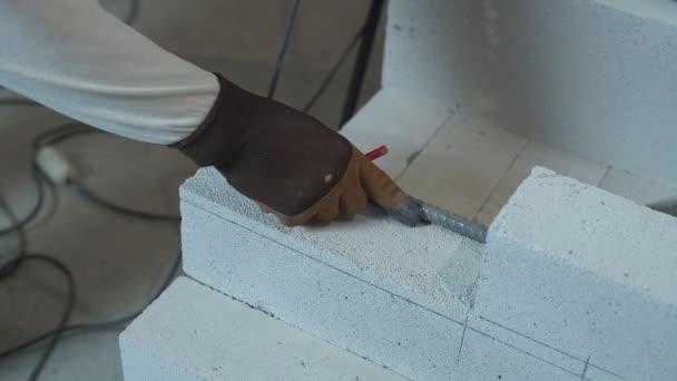 Builder Hände markieren belüfteten Betonblock mit Bleistift und Stahl Ankerstange
