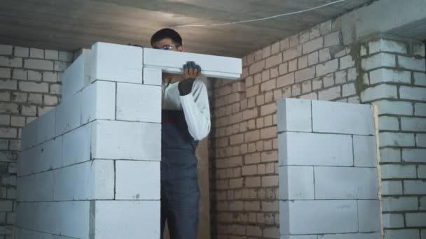 Bauarbeiter bauen Tür mit belüfteten Betonblöcken
