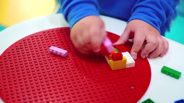 closeup of little child hands building with colorful plastic blocks on table