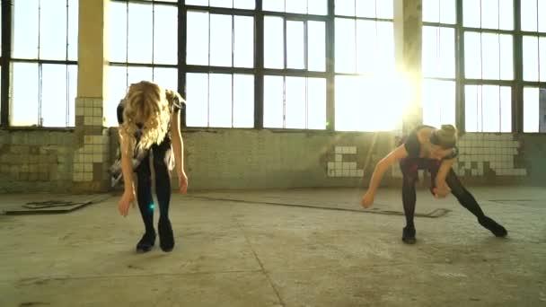Zwei Tänzerinnen proben in alter Fabrikhalle mit Linsenschlag