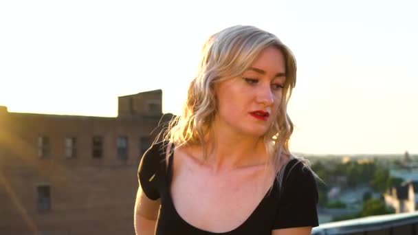 portrait of young blonde woman standing still on roof against sunset