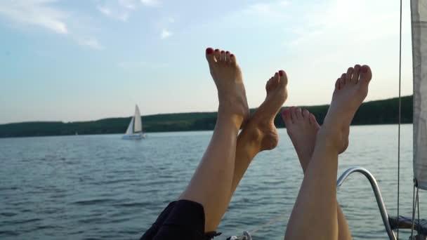 zkřížené nohy dvou žen zvednuté na boku lodi s řekou na pozadí