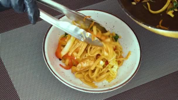 zaostřená šéfkuchařky pro vaření těstovin se zeleninou a filé na talíři
