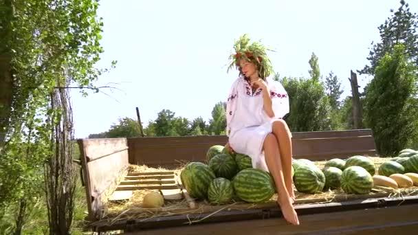 Žena v etnických šatech, která sedí na melounu vodních
