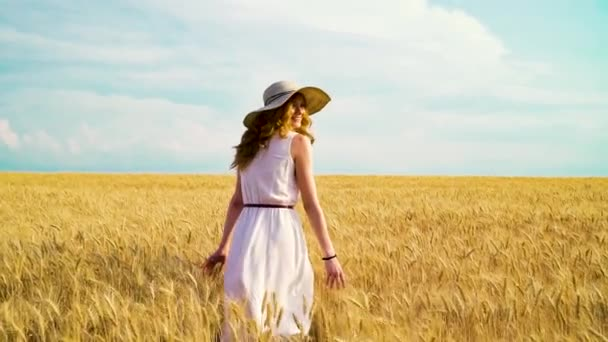 Hezká dívka, která chodí po pšeničném poli v období sklizně